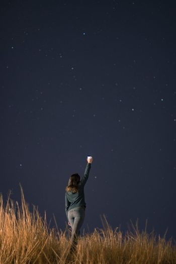 Rear view of young woman with arms raised standing against star field