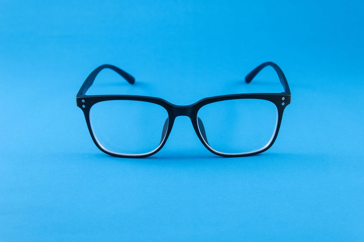 Close-up of eyeglasses against blue background