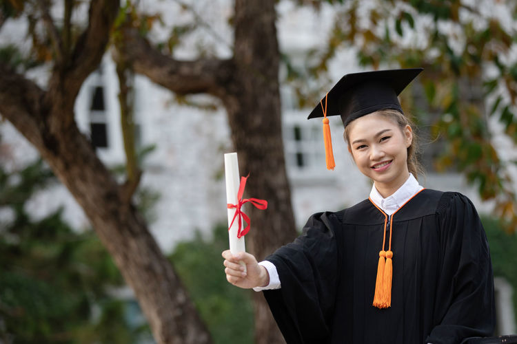 Portrait of smiling student holding diploma while standing outdoors