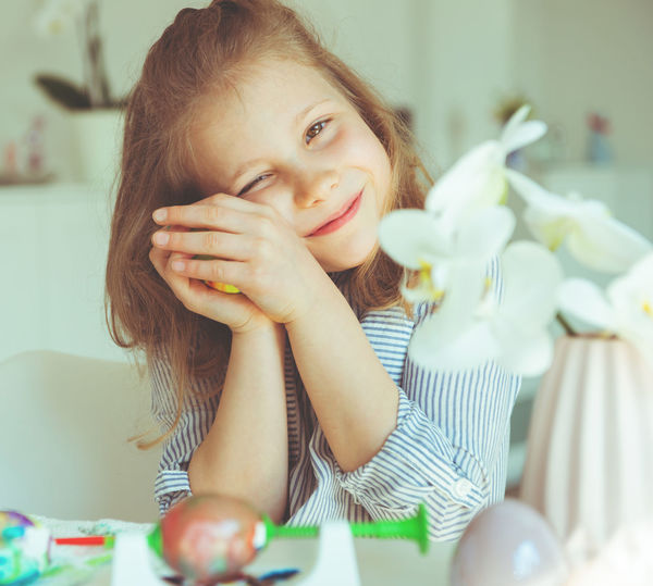 Portrait of cute girl holding easter egg while sitting at home