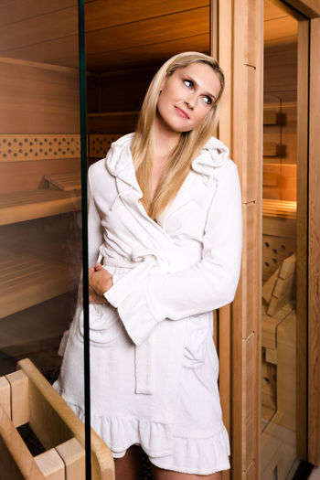 Beautiful young woman wearing bathrobe at beauty spa