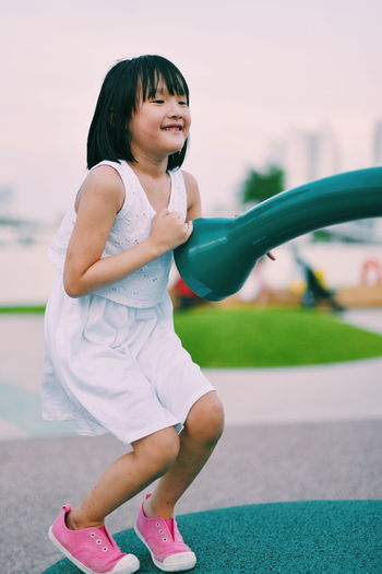 Girl playing on field against sky