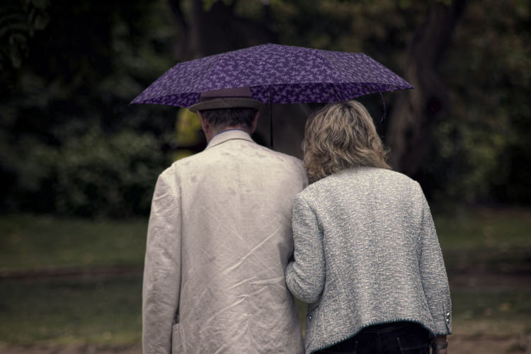 Rear View Of Couple Walking Under Umbrella In Park