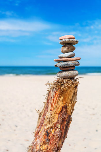 Stack of ZEN stones against blue cloudy sky Balance Balanced Blue Sky Coast Day Harmony Meditation Nature No People Outdoors Pebble Relaxation Sky Spiritual Stability Stack Stacked Stones Therapy Tranquil Scene Tranquility Vertical Zen