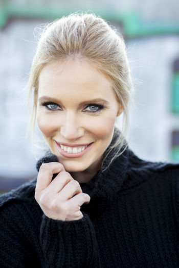 Close-Up Portrait Of Beautiful Woman Smiling While Holding Turtleneck
