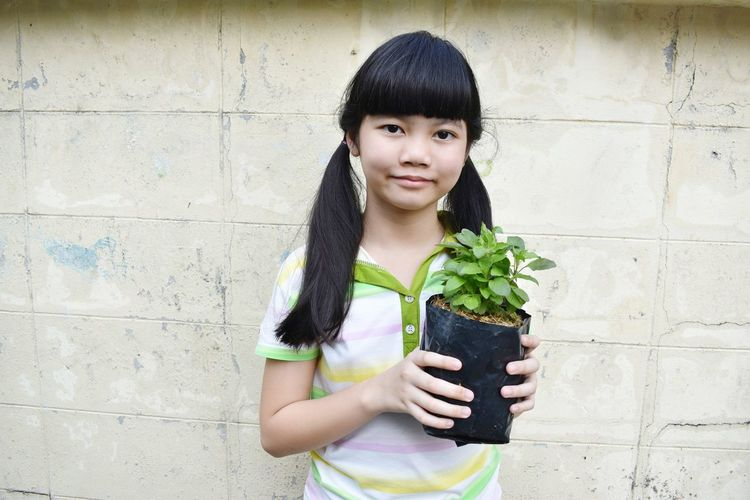 Portrait of smiling girl holding plant against wall