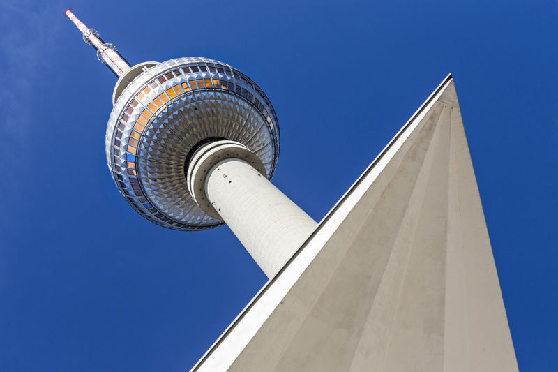 Low Angle View Of Fernsehturm By Triangle Shape Against Blue Sky