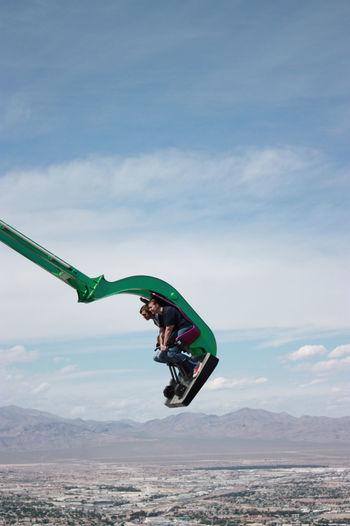 People sitting amusement park ride against sky