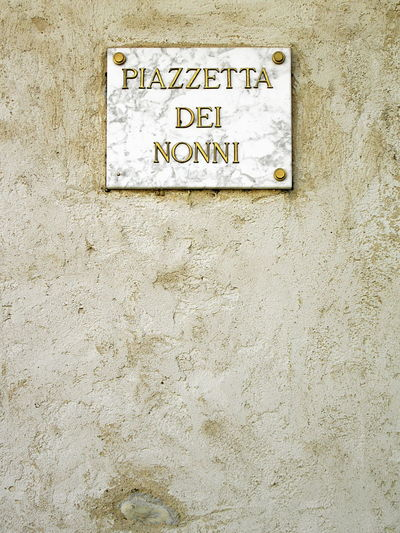 """Full frame shot of old weathered concrete wall with marble plaque with """"Piazzetta dei nonni"""" sign (Italian for """"Grandparents' square"""") Architecture ArchiTexture Close-up Communication Day Grandparents Marble No People Old Outdoors Place Plaque Sign Square Textures And Surfaces Wall Wall - Building Feature Weathered"""