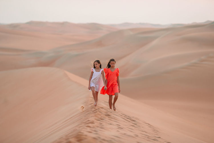 Sisters walking on sand dunes at desert