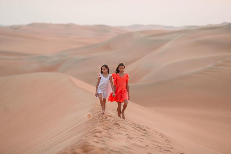 Sisters walking on sand dunes at desert