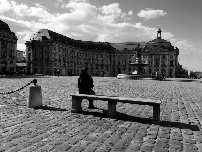 Rear view of woman sitting on bench at place de la bourse