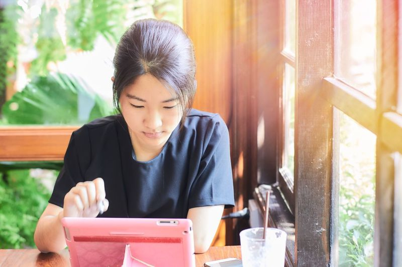 Asian girl using tablet to do her business. Black Hair Window Young Adult Casual Clothing Lifestyles Businesswoman Sitting Indoors  Modern Happiness Asian  Daylight Communication Pretty Connection Social Network Girl Portrait Tablet Computer Wireless Technology Leisure Activity