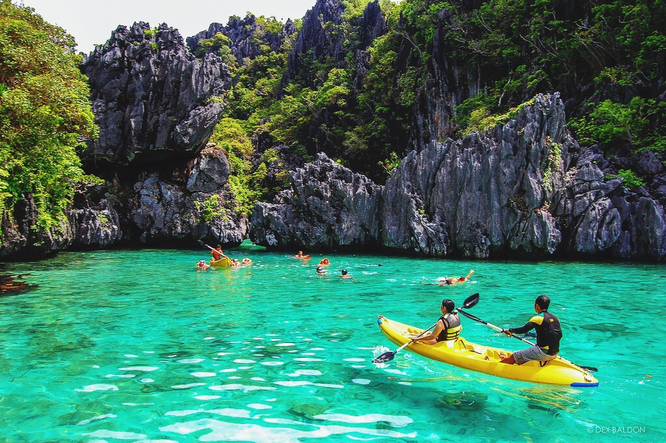 water, nautical vessel, transportation, boat, tranquility, tranquil scene, men, mode of transport, leisure activity, scenics, vacations, tree, sea, nature, waterfront, cliff, person, blue, non-urban scene, rock formation, tourist, beauty in nature, kayak, boating, tourism, fun, adventure