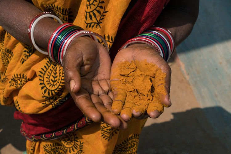 Midsection of woman with turmeric powder on hand