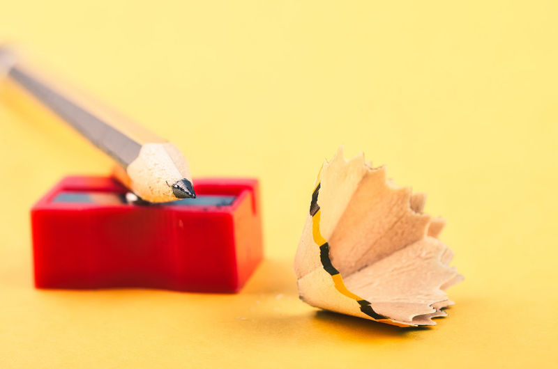 pencil with it shavings and sharpener over yellow background Indoors  Still Life Red Studio Shot Close-up Pencil No People Yellow Colored Background Wood - Material Group Of Objects Focus On Foreground Copy Space Selective Focus School Supplies Sharp Art And Craft Writing Instrument White Background Creativity Matchstick