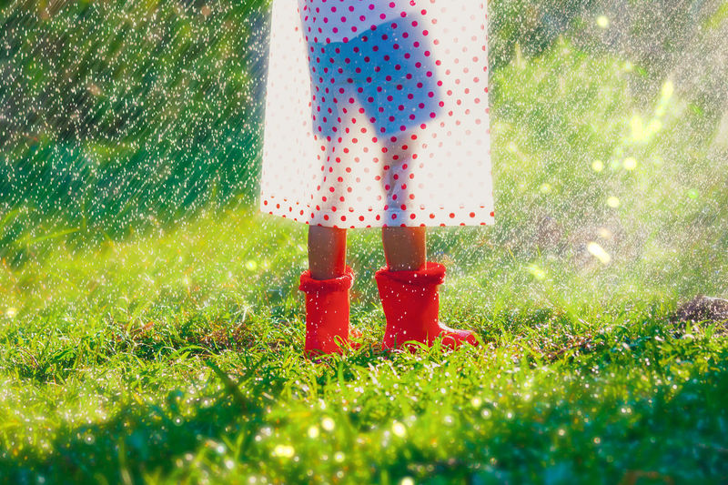 Low section of person wearing rubber boots and raincoat while standing on grass during rainfall