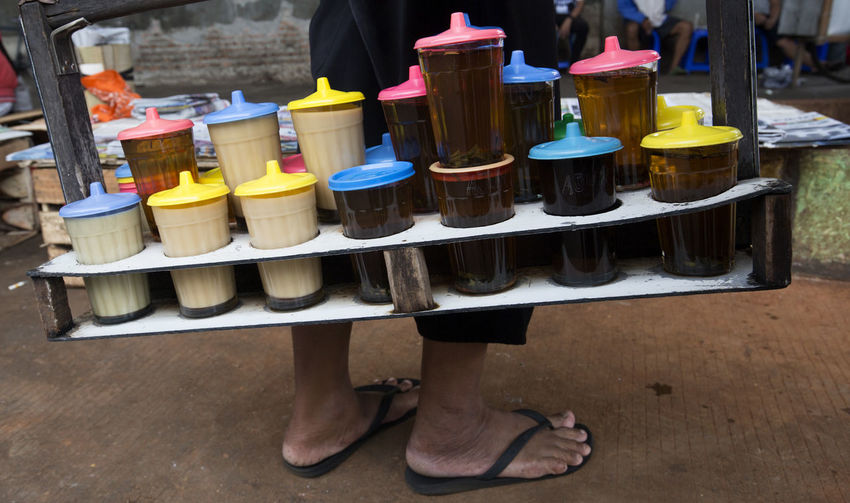 Drinks for Sale Low Section One Person Food And Drink Container Day Food Choice Human Body Part Human Leg Standing Business Freshness Men Retail  Adult Table Midsection Wood - Material Variation Human Foot Tray Beverage For Sale Market Stall Traditional Market Morning Jakarta INDONESIA