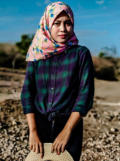 Portrait of young woman wearing hijab standing at beach