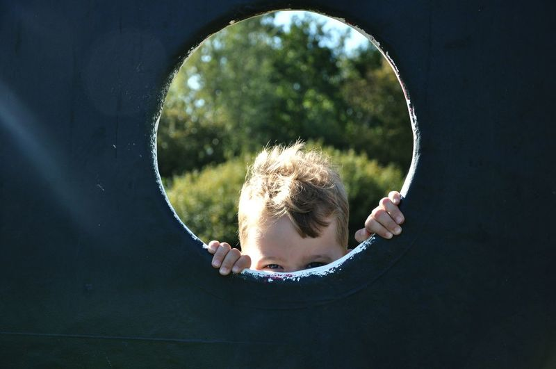 Boy seen through play equipment