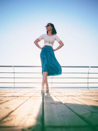 Low angle view of fashionable woman standing with hands on hip at boat deck against sky