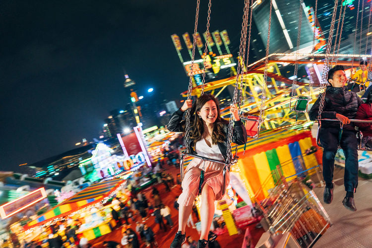 Hong Kong Adult Amusement Park Ride Building Exterior Built Structure Carousel Celebration City City Life Enjoyment Happiness Illuminated Leisure Activity Lifestyles Men Motion Night Outdoors Real People Sky Smiling Traditional Festival Women Young Adult Young Women