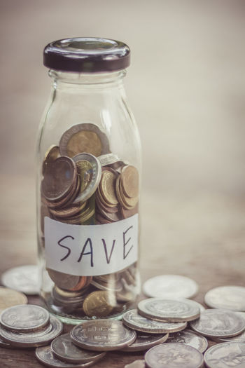 many coin in Glass and save money investment concept Economy Travel Banking Bottle Business Close-up Coin Container Finance Financial Glass - Material Jar Money No People Savings Still Life Table Text Transparent Wealth