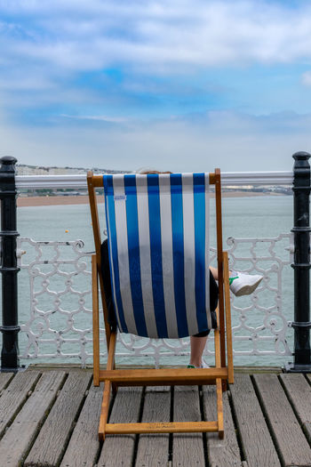 Rear view of woman sitting on chair against railing at beach