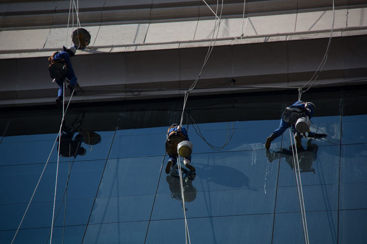 Low angle view of men working on rope