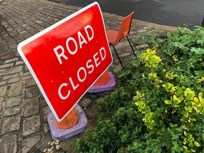 Road Closed Sign Sign Road Closed Closed Text Western Script Communication Sign Red High Angle View Capital Letter No People Day Plant Warning Sign Information Nature Green Color Guidance Information Sign Outdoors Script Road