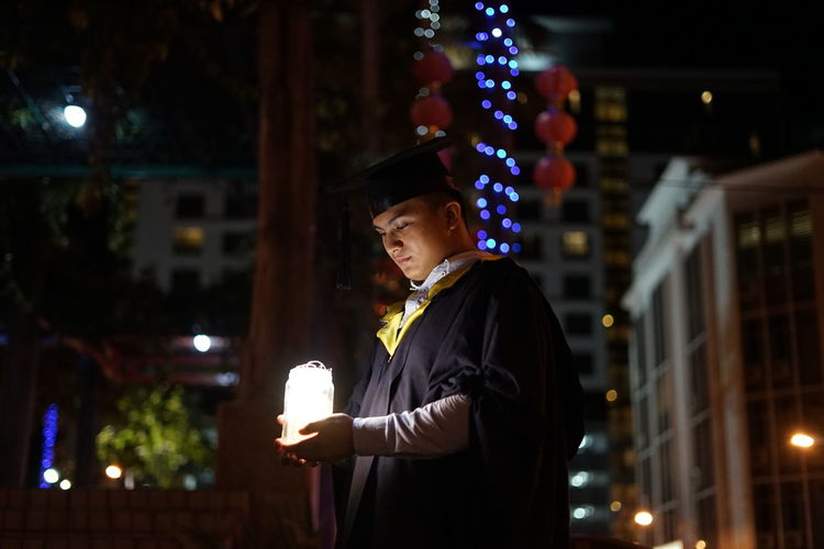 Young man wearing graduation gown at night