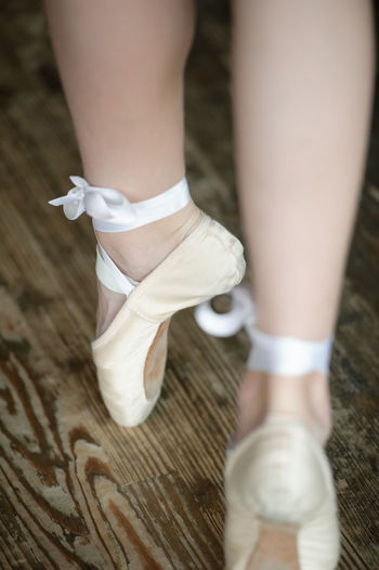 Low Section Of Woman Wearing Ballet Shoes Dancing On Hardwood Floor