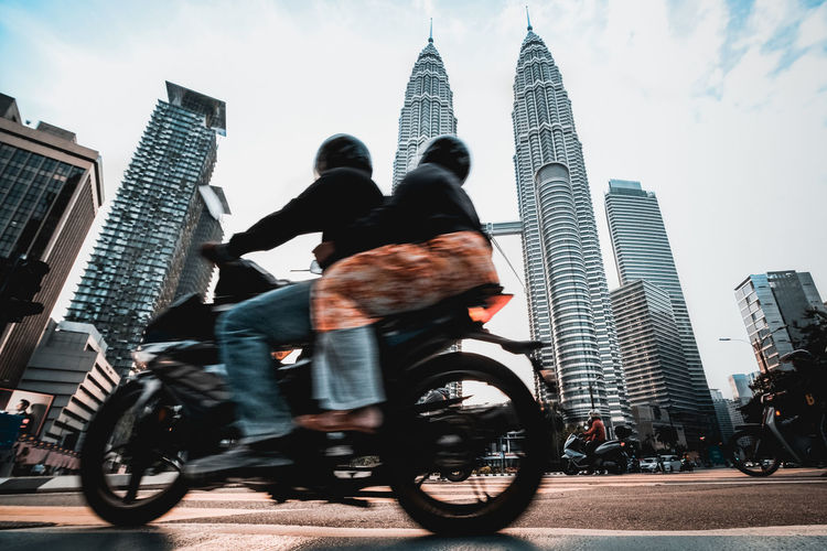 Low Angle View Of People Riding Motorcycle On Street Against Petronas Towers