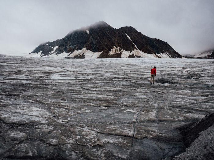 Rear view of hiker walking on rough landscape