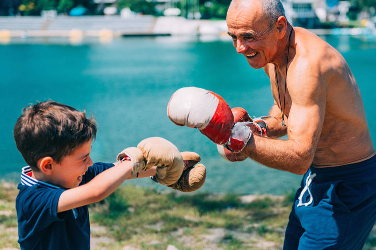 Boxing By The Lake Boxing Boxing Gloves Boxing Training Boxing Match Boxing Man Boy Outdoors Boxing Sparring Sport Boxing Class Senior 60s 6-7 Years Men Kid Family Grandson Grandfather Trainer Training Boxer Fighter Smiling Happy Lake