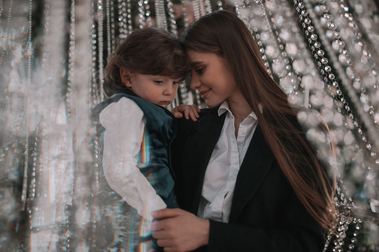 Portrait of woman with daughter against blurred background