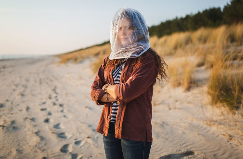 Portrait of young woman with face covered by plastic bag standing at beach