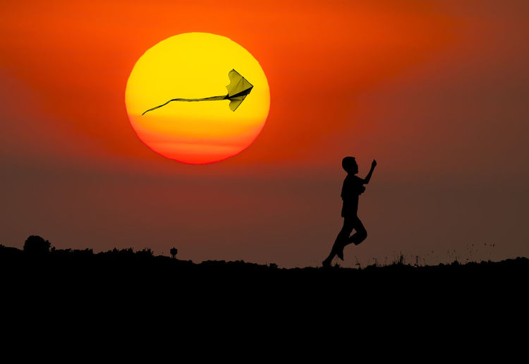 Silhouette boy flying kite while running on field against sun during sunset