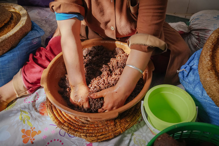 Local moroccan woman hand-kneading argan oily paste to extract argan oil. essaouira, morocco.