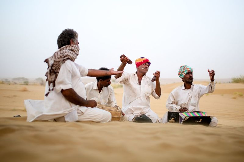 Desert musicians Men Sitting Traditional Clothing Group Of People Real People People Women Lifestyles Celebration Nature Full Length Clothing Outdoors