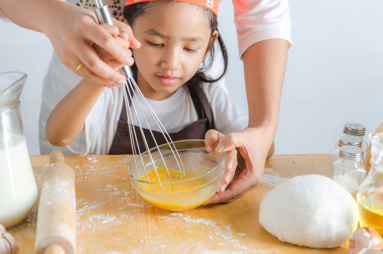 Batter Bowl Childhood Concentration Domestic Kitchen Dough Egg Elementary Age Flour Food Food And Drink Girls Holding Indoors  Lifestyles Looking Down Making Mixing Mixing Bowl Preparation  Preparing Food Real People Rolling Pin Table Wire Whisk
