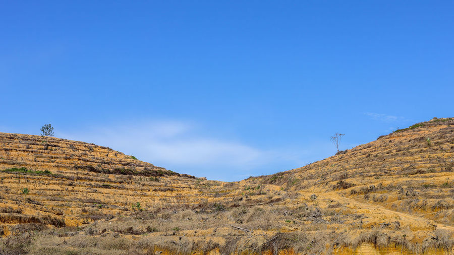 Minimalist landscape of bright blue sky and yellow ground Sky Tranquil Scene Tranquility Scenics - Nature Beauty In Nature Mountain Nature Environment Landscape Day Non-urban Scene Blue Copy Space No People Outdoors Remote Idyllic Rock Arid Climate Land Cloud - Sky