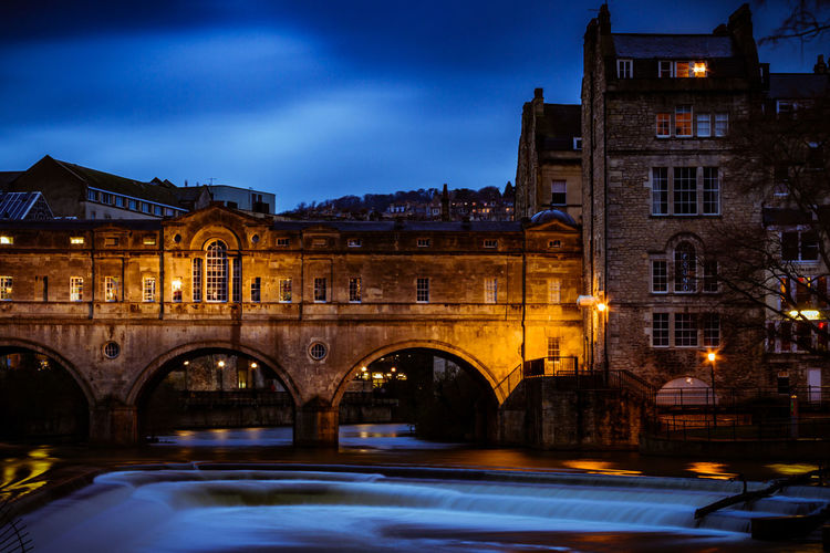 Long exposure of Pulteney Weir and Bridge in Bath Arch Architecture Blue Color Bridge Bridge - Man Made Structure Building Exterior Built Structure City Contrast Flowing Water Historical Building Illuminated Long Exposure Night Night Photography Nightphotography No People Orange Color River Sky Travel Destinations Weir