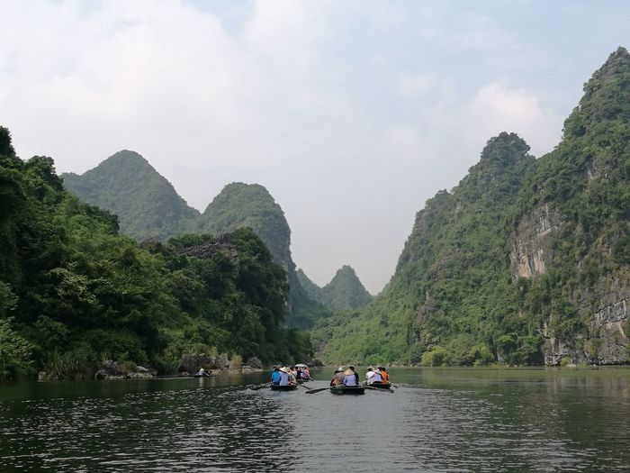 People in boats on river amidst mountains against sky