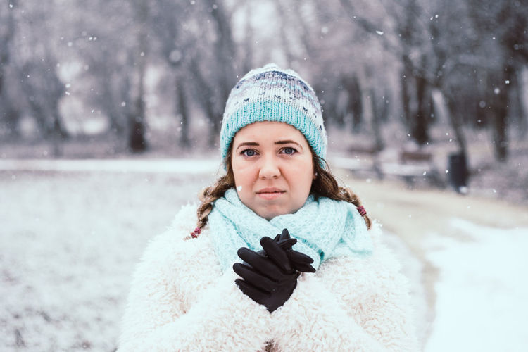 Portrait of young woman standing at park during winter