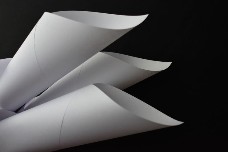 Low angle view of white paper against black background