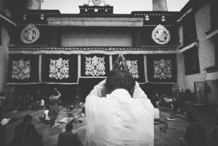 A man praying in old of the oldest template in Lhasa Praying Portrait Spirituality Headshot Waist Up Building Exterior Women Place Of Worship Belief Religion Adult Built Structure Architecture Leisure Activity People Lifestyles Men Real People Rear View EyeEm Selects