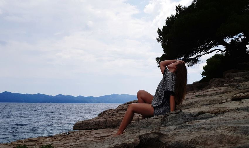 Side view of young woman sitting on rock at shore against sky