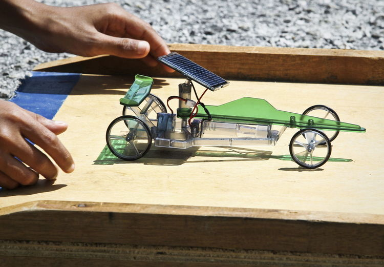 Cropped hand holding vehicle model with solar panel