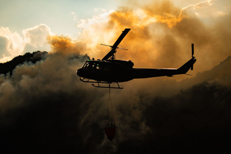 Low angle view of silhouette helicopter against smoke during sunset